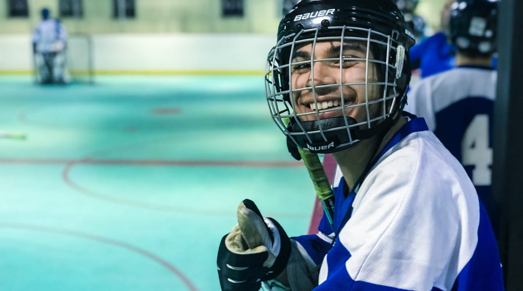 Boy giving a thumbs up by hockey rink