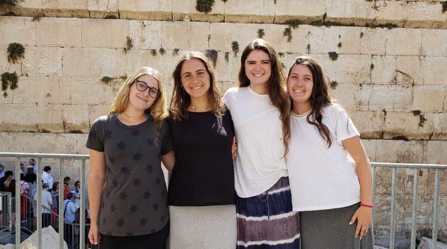 Teen girls smiling by Israeli wall