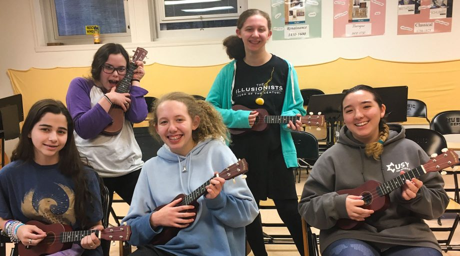 High school girls playing ukulele in school club